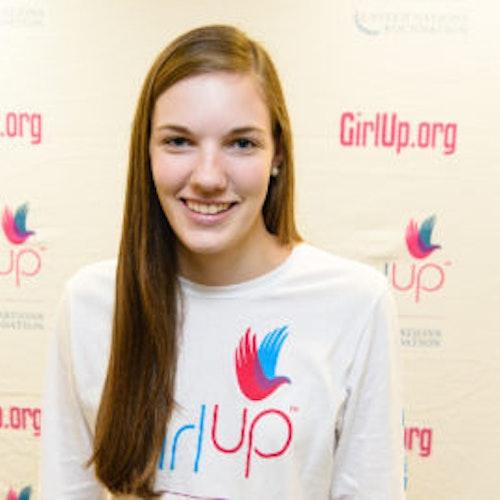 """Kate McCollum, consultora adolescente de 2013-2014 (foto de perto, um pouco desfocada). Uma adolescente sorridente olhando para a câmera, tendo uma parede com """"girlup.org"""" no plano de fundo. Ela está usando a camiseta toda branca da Girl Up"""