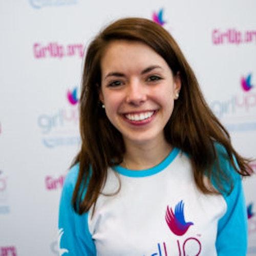 """Katherine Cochran, do grupo fundador de consultoras adolescentes (foto de rosto, sem nitidez). Uma adolescente sorridente olhando para a câmera, tendo uma parede com """"girlup.org"""" no plano de fundo. Ela está usando a camiseta branca de manga comprida azul da Girl Up"""