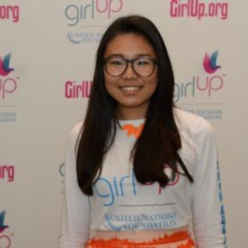 """Kyung Mi Lee, copresidente, consultora adolescente de 2016-2017 (foto de meio-corpo, desfocada), sorridente olhando para a câmera, tendo uma parede com """"girlup.org"""" no plano de fundo. Ela está usando a camiseta toda branca da Girl Up"""