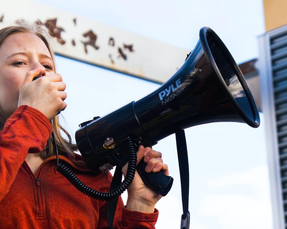 (Ángulo cerrado) Eva Jones, Grupo de Consejeras adolescentes 2018-2019, sosteniendo un megáfono.