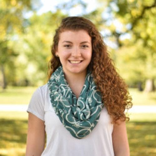 Leah Adelman, consultora adolescente de 2016-2017 (foto de meio-corpo em ângulo amplo, desfocada) sorridente olhando para a câmera, tendo o verde das plantas como plano de fundo