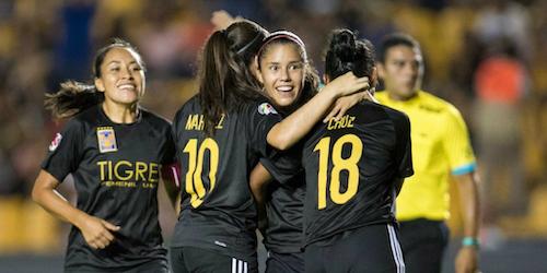 4 mulheres na foto – as integrantes da equipe mexicana de futebol feminino Tigres estão felizes e dão um abraço coletivo no campo