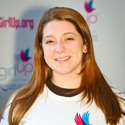 """Lucy Lohrmann, Cidade natal: Hasbrouck Heights, Nova Jersey, 2011-2012, segundo grupo de consultoras adolescentes (foto de perto). Uma adolescente sorridente olhando para a câmera, tendo uma parede com """"girlup.org"""" no plano de fundo. Ela está usando a camiseta toda branca da Girl Up"""