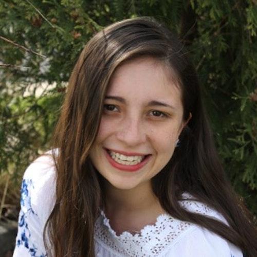 Maria Aldana, consultora adolescente de 2016-2017 (foto de rosto em close muito próximo) sorridente olhando para a câmera e tendo o verde das plantas como plano de fundo
