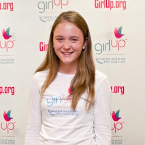 """Meghan Murray, Cidade natal: Chevy Chase, MD, consultora adolescente de 2012-2013 (foto de perto, um pouco desfocada). Uma adolescente sorridente olhando para a câmera, tendo uma parede com """"girlup.org"""" no plano de fundo. Ela está usando a camiseta toda branca da Girl Up"""