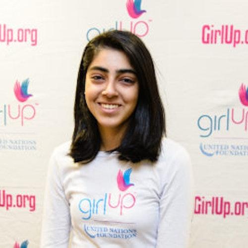 """Mehar Gujral, consultora adolescente de 2013-2014 (foto de perto, um pouco desfocada). Uma adolescente sorridente olhando para a câmera, tendo uma parede com """"girlup.org"""" no plano de fundo. Ela está usando a camiseta toda branca da Girl Up"""