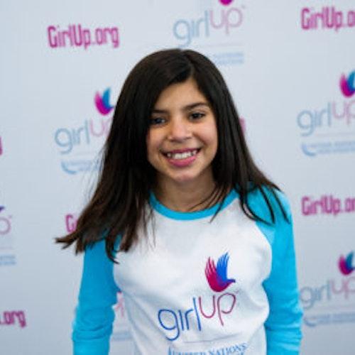 """Mia Gutierrez, da classe fundadora de consultoras adolescentes (foto de perto, sem nitidez). Uma adolescente sorridente olhando para a câmera, tendo uma parede com """"girlup.org"""" no plano de fundo. Ela está usando a camiseta branca de manga comprida azul da Girl Up"""