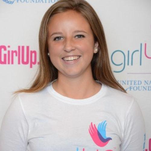 """Morgan Wood, consultora adolescente de 2014-2015 (foto do rosto em close, um pouco desfocada). Uma adolescente sorridente olhando para tendo uma parede com """"girlup.org"""" no plano de fundo. Ela está usando a camiseta toda branca da Girl Up"""