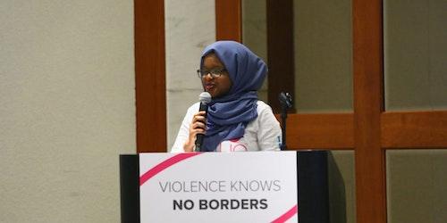Munira Alimire, Jeune conseillère, tenant un micro et parlant derrière le podium, devant un panneau sur lequel est écrit «violence knows no borders»