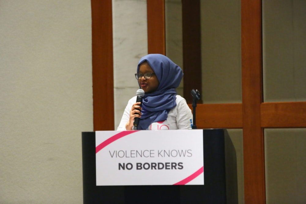 """Munira Alimire teen adviser holding a mic and speaking behind the podium, in the front of the podium a sign """"violence knows no borders"""""""