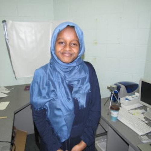 Munira Alimire, consultora adolescente de 2017-2018 (foto de meio-corpo, desfocada) tendo um laboratório como plano de fundo. Ela está usando um hijab azul