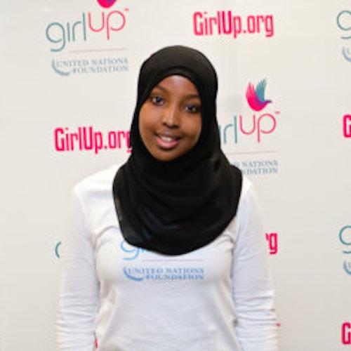 """Munira Khalif, Cidade natal: Fridley, MN, consultora adolescente de 2012-2013 (foto de perto, um pouco desfocada). Uma adolescente sorridente olhando para a câmera, tendo uma parede com """"girlup.org"""" no plano de fundo. Ela está usando a camiseta toda branca da Girl Up"""