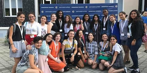 une photo de groupe de jeunes filles devant le tableau de l'événement WiSci