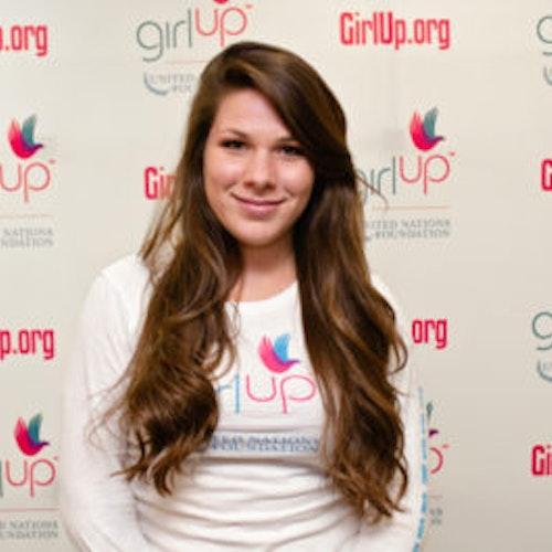 """Natasha Madorsky, Cidade natal: Cleveland, OH, consultora adolescente de 2012-2013 (foto do rosto em close, um pouco desfocada). Uma adolescente sorridente olhando para a câmera, tendo uma parede com """"girlup.org"""" no plano de fundo. Ela está usando a camiseta toda branca da Girl Up"""