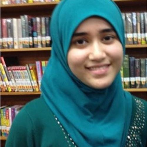 Noorhan Amani, consultora adolescente de 2015-2016 (foto de perto), sorridente olhando para a câmera. Ela está usando um hijab verde