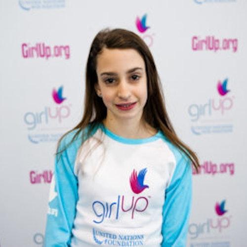 """Olivia Layton, do grupo fundador de consultoras adolescentes (foto de perto, sem nitidez). Uma adolescente sorridente olhando para a câmera, tendo uma parede com """"girlup.org"""" no plano de fundo. Ela está usando a camiseta branca de manga comprida azul da Girl Up"""
