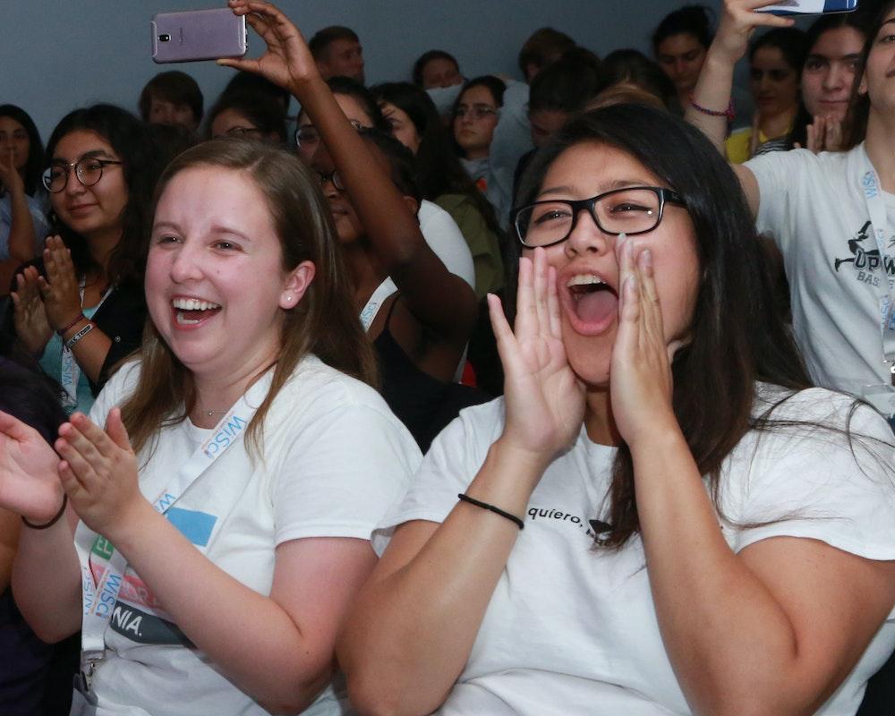 Quatro funcionárias da Girl Up batendo palmas e vibrando no público