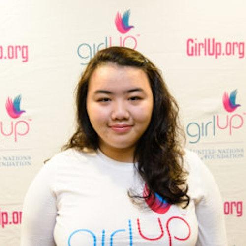 """Priscilla Guo, consultora adolescente de 2013-2014 (foto de perto, um pouco desfocada). Uma adolescente sorridente olhando para a câmera, tendo uma parede com """"girlup.org"""" no plano de fundo. Ela está usando a camiseta toda branca da Girl Up"""