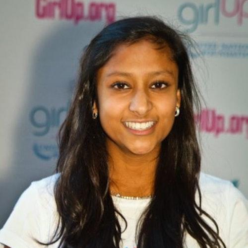 """Priyanka Jain, Cidade natal: Bellevue, Washington, 2011-2012, segundo grupo de consultoras adolescentes (foto de perto). Uma adolescente sorridente olhando para a câmera, tendo uma parede com """"girlup.org"""" no plano de fundo. Ela está usando a camiseta toda branca da Girl Up"""