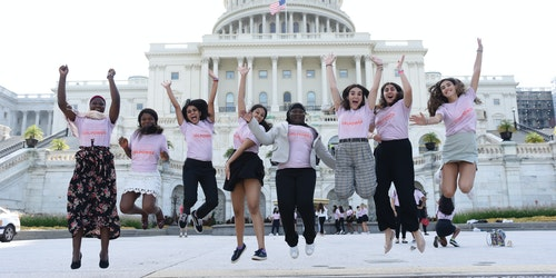 full angle shot of a group of Girl Up girls with a different ethnic group do a jumping picture in front of the capitol in DC