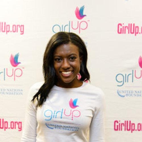 """Raven Delk, consultora adolescente de 2013-2014 (foto de perto, um pouco desfocada). Uma adolescente sorridente olhando para a câmera, tendo uma parede com """"girlup.org"""" no plano de fundo. Ela está usando a camiseta toda branca da Girl Up"""