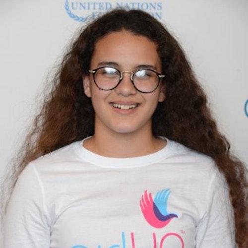 """Rebecca Ruvalcaba, consultora adolescente de 2014-2015 (foto do rosto em close, um pouco desfocada). Uma adolescente sorridente olhando para tendo uma parede com """"girlup.org"""" no plano de fundo. Ela está usando a camiseta toda branca da Girl Up"""