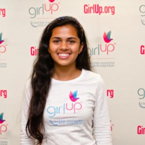 """Riya Singh, consultora adolescente de 2012-2013 (foto de perto, um pouco desfocada). Uma adolescente sorridente olhando para a câmera, tendo uma parede com """"girlup.org"""" no plano de fundo. Ela está usando a camiseta toda branca da Girl Up"""