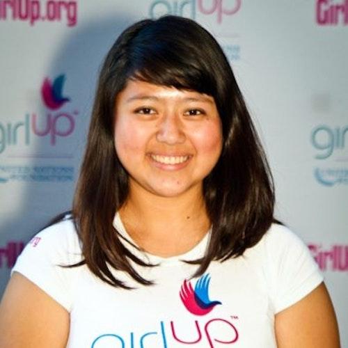 """Rocio Ortega, Cidade natal: Los Angeles, CA, 2011-2012, segundo grupo de consultoras adolescentes (foto de perto). Uma adolescente sorridente olhando para a câmera, tendo uma parede com """"girlup.org"""" no plano de fundo. Ela está usando a camiseta toda branca da Girl Up"""