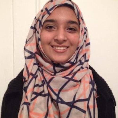 Sabah Hussain, consultora adolescente de 2015-2016 (foto de perto), sorridente olhando para a câmera. Ela está usando um hijab cinza