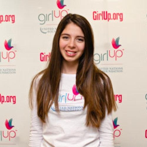 """Sarah Gale, copresidente, consultora adolescente de 2013-2014 (foto de perto, um pouco desfocada). Uma adolescente sorridente olhando para a câmera, tendo uma parede com """"girlup.org"""" no plano de fundo. Ela está usando a camiseta toda branca da Girl Up"""