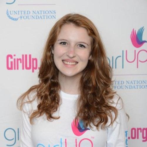 """Sarah Gordon, consultora adolescente de 2014-2015 (foto de perto). Uma adolescente sorridente olhando para a câmera, tendo uma parede com """"girlup.org"""" no plano de fundo. Ela está usando a camiseta toda branca da Girl Up"""