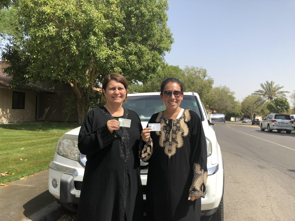 two Saudi women are holding their driver license in front of the car with big smiles