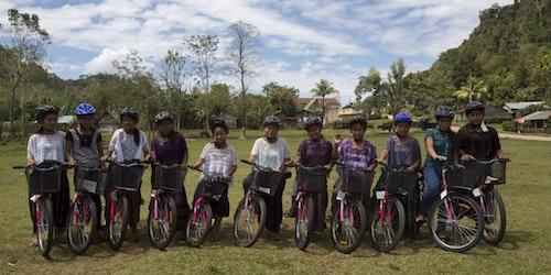 Foto de um grupo de meninas sorridentes em suas bicicletas, usando capacete
