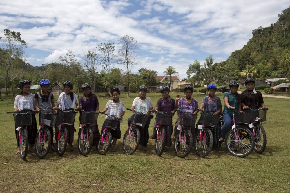 a group pictures with girls with a big smile on their face on their bicycle and helmet on