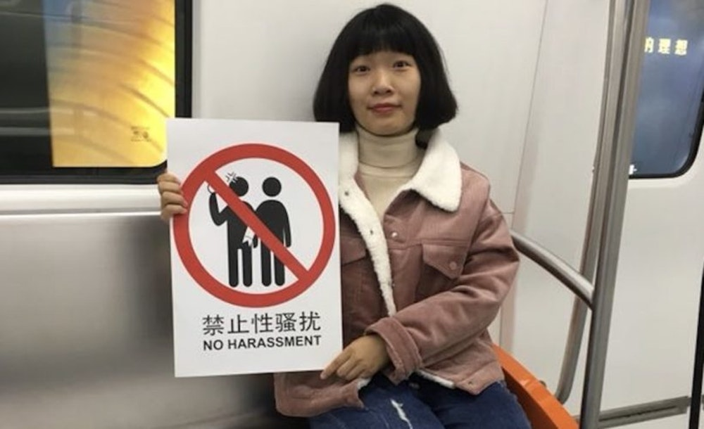 "a Chinese girl is sitting down on the metro seat, facing the camera and holding a sign ""no harassment."""