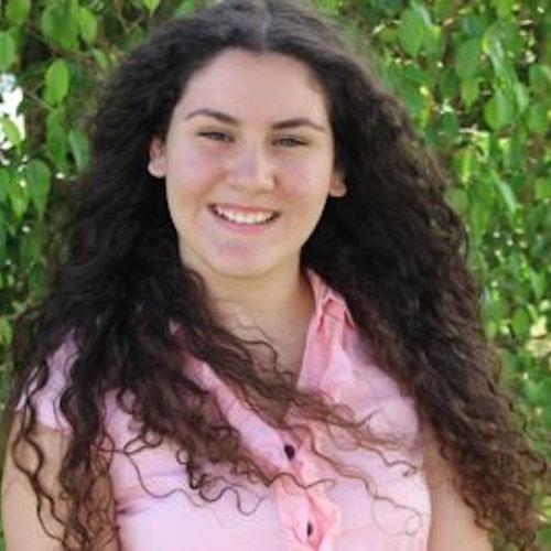 Shayla Zamora, consultora adolescente de 2016-2017 (foto de perto, um pouco desfocada) sorridente olhando para a câmera e tendo o verde das plantas como plano de fundo