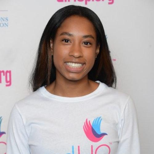 """Simone Cowan, consultora adolescente de 2014-2015 (foto de perto). Uma adolescente sorridente olhando para a câmera, tendo uma parede com """"girlup.org"""" no plano de fundo. Ela está usando a camiseta toda branca da Girl Up"""