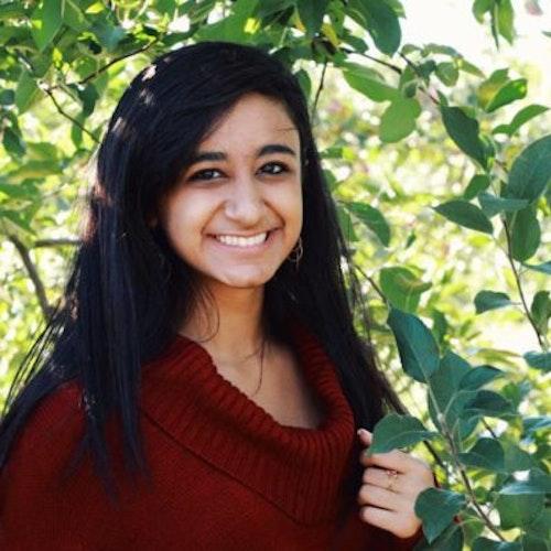 Sarina Divan, consultora adolescente de 2016-2017 (foto de perto). Uma selfie sorridente olhando para a câmera e tendo o verde das plantas como plano de fundo