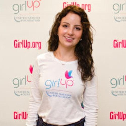 """Sofia Stafford, Cidade natal: Nova York, NY, consultora adolescente de 2012-2013 (foto de perto, um pouco desfocada). Uma adolescente sorridente olhando para a câmera, tendo uma parede com """"girlup.org"""" no plano de fundo. Ela está usando a camiseta toda branca da Girl Up"""