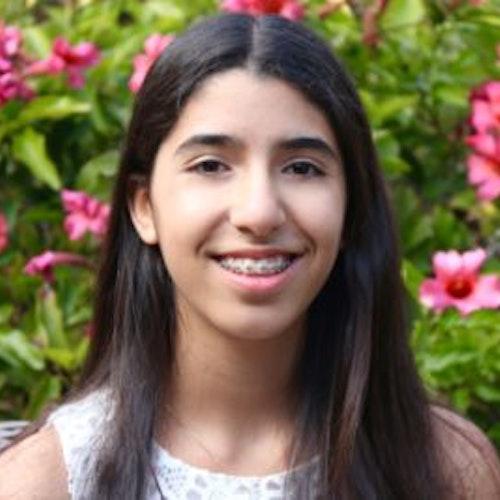 Sophia Danielpour, consultora adolescente de 2016-2017 (foto em close do rosto) sorridente olhando para a câmera. O plano de fundo é o verde das plantas com flores vermelhas