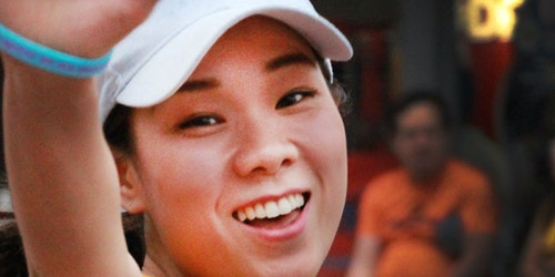 a close cutoff shot of a girl wearing tennis clothes and smile straight to the picture