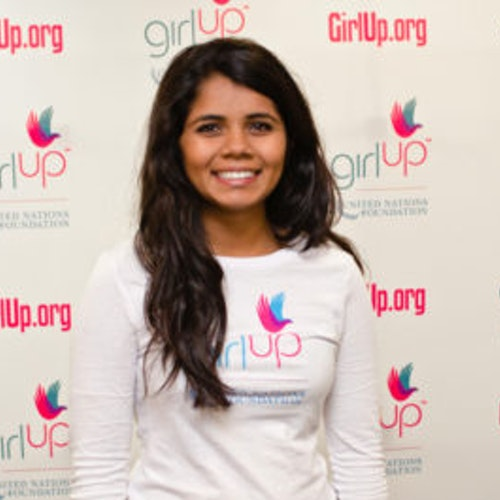 Sri Muppidi Hometown: Pleasanton, CA_2012-2013 Class Teen Advisors (close angle headshot, a little blurry picture ) a teen girl wearing her girl up white shirt with her smiley face facing the camera, and background is girlup.org board