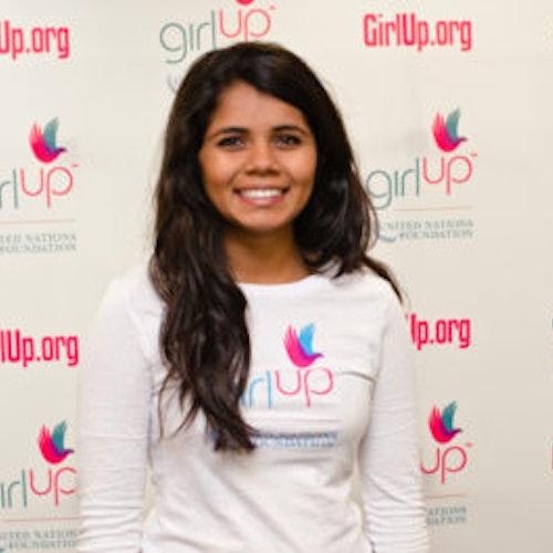"""Sri Muppidi, Cidade natal: Pleasanton, CA, consultora adolescente de 2012-2013 (foto do rosto em close, um pouco desfocada). Uma adolescente sorridente olhando para a câmera, tendo uma parede com """"girlup.org"""" no plano de fundo. Ela está usando a camiseta toda branca da Girl Up"""