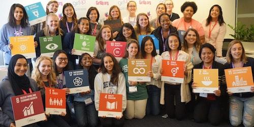 Meninas da Girl Up segurando placas com as metas de desenvolvimento sustentável no evento da Girl Up