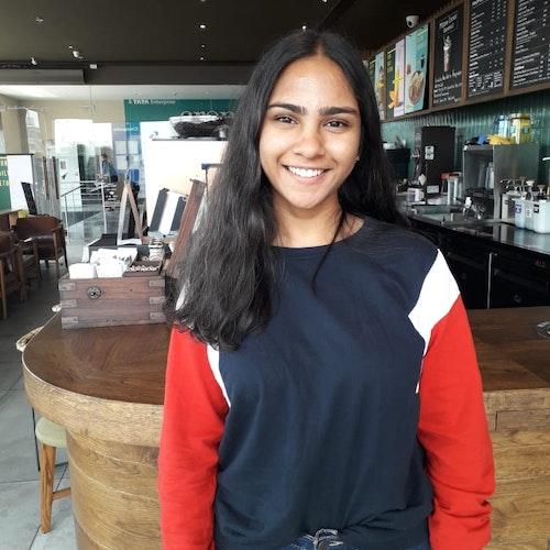Tanushah Ramadass, consultora adolescente de 2019-2020 (foto de meio-corpo), sorridente olhando para a câmera, tendo uma cafeteria como plano de fundo