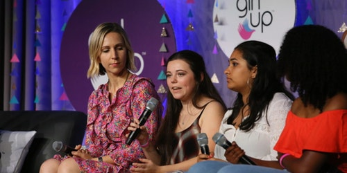 3 girls are sitting down on the couch on the stage and speaking with their mic on their hand