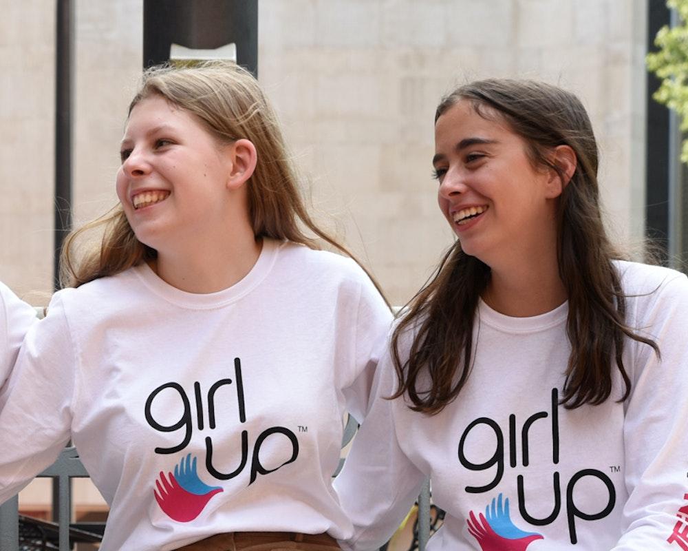 4filles d'ethnies différentes de la communauté GirlUp portant des maillots GirlUp et ayant chacune les mains autour du dos de l'autre (photo de groupe)