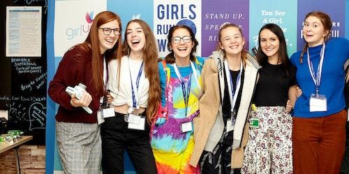 Uma foto de um grupo de meninas da Girl Up com as mãos nas costas das amigas ao lado, em frente à placa do evento da Cúpula