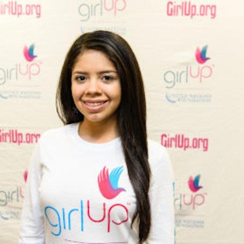 """Valeria Hansen, consultora adolescente de 2013-2014 (foto de perto, um pouco desfocada). Uma adolescente sorridente olhando para a câmera, tendo uma parede com """"girlup.org"""" no plano de fundo. Ela está usando a camiseta toda branca da Girl Up"""