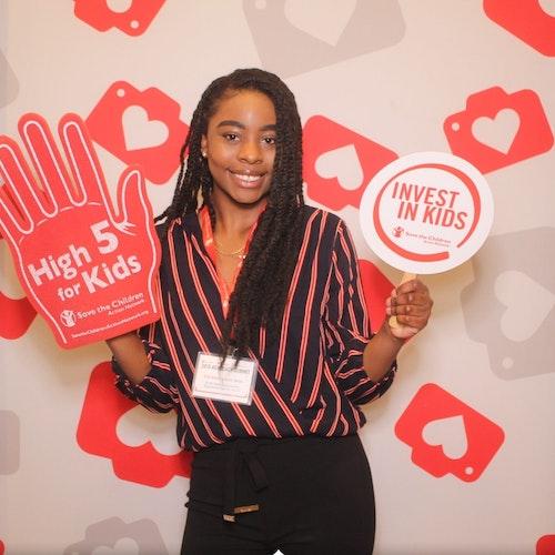"""Vanessa Louis-Jean, consultora adolescente de 2019-2020 (foto em plano americano) sorridente olhando para a câmera e segurando as placas """"High 5 for kids"""" (Comemorando com as crianças) e """"Invest in kids"""" (Invista nas crianças)"""